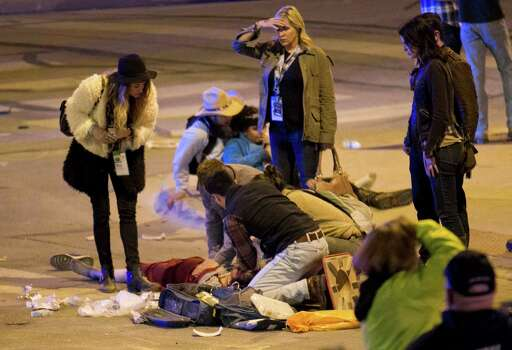 People perform CPR on a woman after she was struck by a vehicle on Red River Street in downtown Austin, Texas, at SXSW on Wednesday March 12, 2014. Her condition is unknown. Police say two people have died after a car drove through temporary barricades set up for the South By Southwest festival and struck a crowd of pedestrians. Photo: Jay Janner, AP Photo/Austin American-Statesman/Statesman.com / Austin American-Statesman