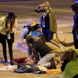 People perform CPR on a woman after she was struck by a vehicle on Red River Street in downtown Austin, Texas, at SXSW on Wednesday March 12, 2014. Her condition is unknown. Police say two people have died after a car drove through temporary barricades set up for the South By Southwest festival and struck a crowd of pedestrians.
