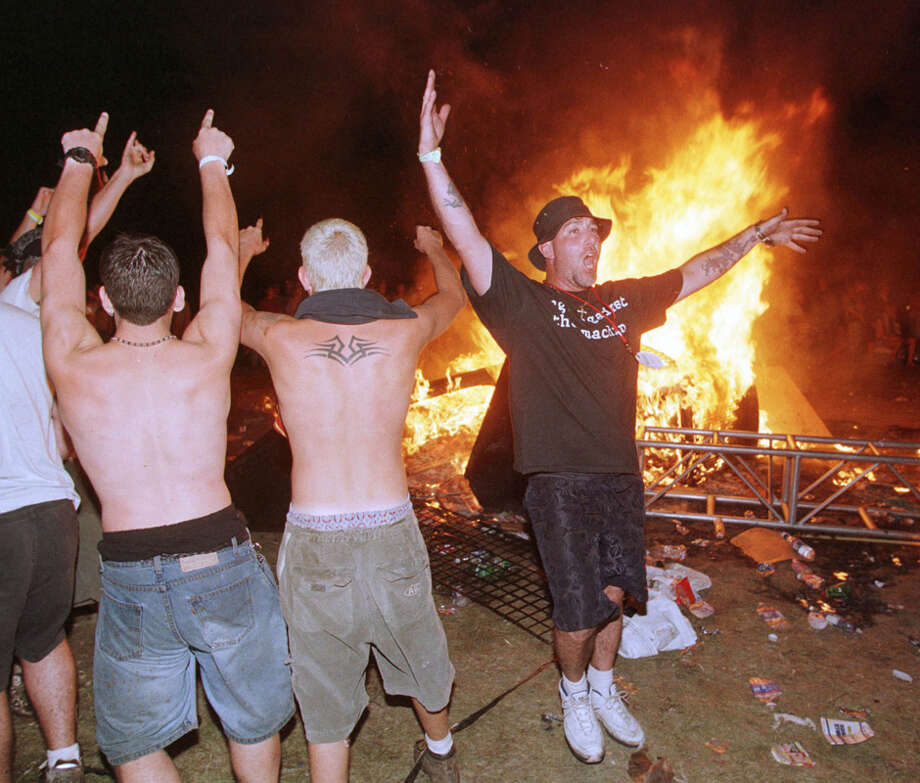 "Woodstock '99 (July 22-25, 1999 – Rome, N.Y.): Temperatures reaching above 100 degrees, no shade, overpriced water and too few bathrooms create a bad vibe among some members of the crowd, who are there to watch a lineup filled more with metal acts than the peaceful hippie music of 30 years before. Violence breaks out during a Saturday night performance by Limp Bizkit – then fires. MTV removes its crew there to cover the festival when audience members start ripping plywood panels from security fencing to start more fires and begin looting merchandise booths. Police investigate several instances of rape, including a report of a gang-rape of a woman pulled into the audience while crowd-surfing. Twelve trailers, a small bus and several portable toilets are burned. Six people are injured. Said MTV's Kirt Loder: ""It was dangerous to be around. The whole scene was scary. There were just waves of hatred bouncing around the place, (...) It was clear we had to get out of there.... It was like a concentration camp. To get in, you get frisked to make sure you're not bringing in any water or food that would prevent you from buying from their outrageously priced booths. You wallow around in garbage and human waste. There was a palpable mood of anger.""(Photo by Joe Traver/Newsmakers) Photo: Joe Traver, Getty Images / Hulton Archive"