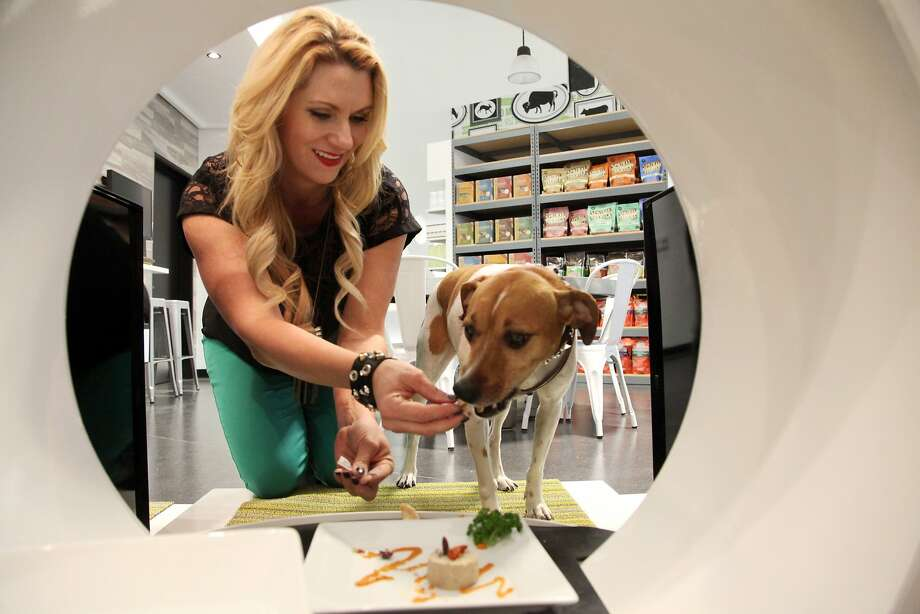 FILE - In This Jan. 2, 2014 file photo, store co-owner, Janene Zakrajsek feeds a dog a gourmet meal at the Pussy & Pooch Pet Lifestyle Center store in Beverly Hills, Calif. An industry spokesman said Americans spent an all-time high of $55.7 billion on their pets in 2013 and will creep close to $60 billion this year on Thursday, March 13, 2014. (AP Photo/Nick Ut, File) Photo: Nick Ut, Associated Press