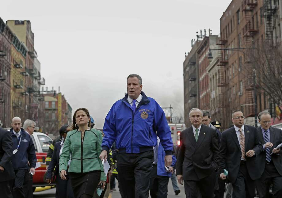 New York Mayor Bill de Blasio (center) and City Council speaker Melissa Mark-Viverito visit the site of the blast that killed at least eight people. Photo: Peter Foley, Bloomberg
