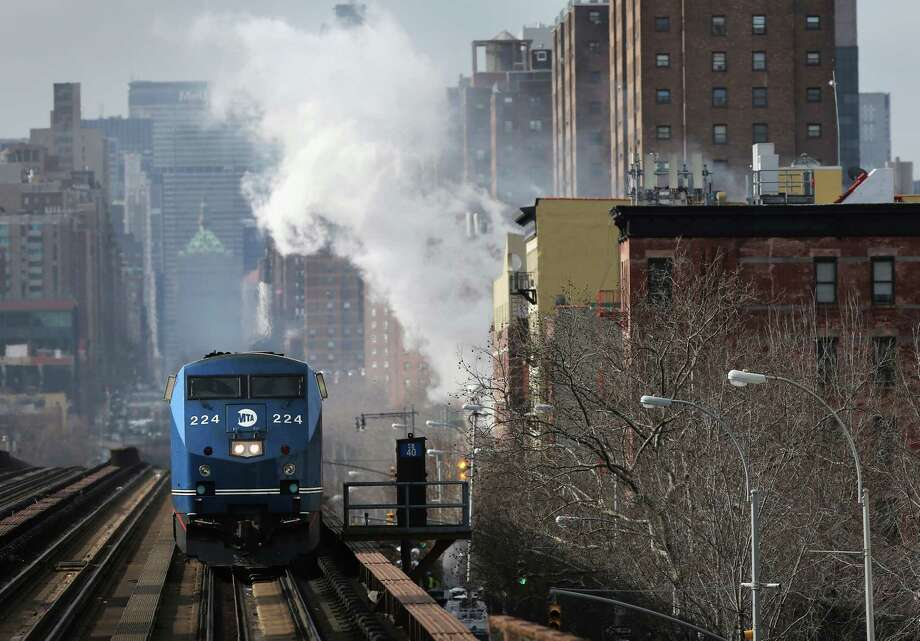 A Metro North train passes the smoking site of an explosion in East Harlem on March 13, 2014 in New York City. At least 7 people were killed, according to reports, in Wednesday's explosion which collapsed two buildings on Park Avenue at 116th Street. Photo: John Moore/Getty Images, Getty Images / Getty Images