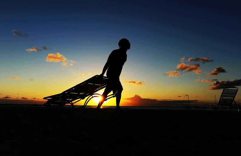 A worker drags away beach chairs in order to store them overnight as the sun sets in Bridgetown,