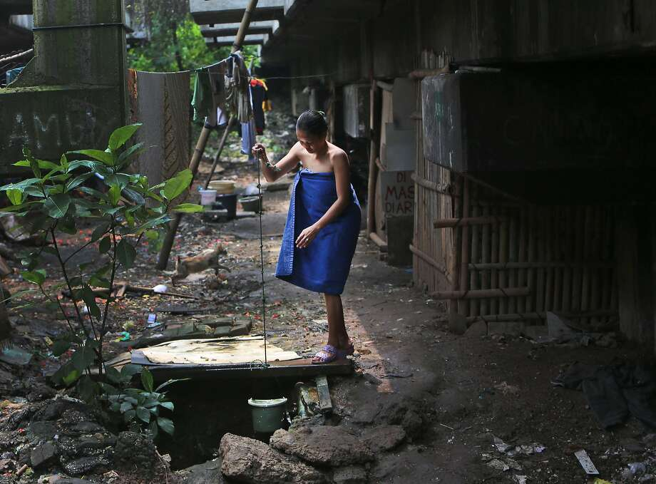 Indoor plumbing is still a luxury: An Indonesian woman collects water for her shower from a well at a slum under an 