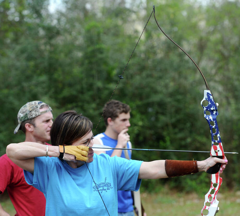 Shana Wilson-Sattler, front, takes careful aim downrange as she, her brother Shea Sattler, left rear, and nephew Gage, 15, right rear, shoot Tuesday. Sour Lake is home to a family of world champion archers -- Shana Wilson-Sattler, her brother Shea Sattler, and his sons, Gage, 15, and Gunner, 7. The four use traditional longbows and recurve bows in competition and to hunt. Photo taken Tuesday, 3/11/14 Jake Daniels/@JakeD_in_SETX Photo: Jake Daniels / ©2014 The Beaumont Enterprise/Jake Daniels
