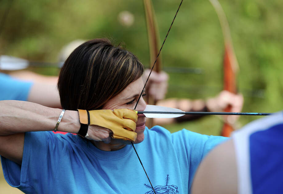 Shana Wilson-Sattler takes aim at a target on her brother's range in Sour Lake on Tuesday. Sour Lake is home to a family of world champion archers -- Shana Wilson-Sattler, her brother Shea Sattler, and his sons, Gage, 15, and Gunner, 7. The four use traditional longbows and recurve bows in competition and to hunt. Photo taken Tuesday, 3/11/14 Jake Daniels/@JakeD_in_SETX Photo: Jake Daniels / ©2014 The Beaumont Enterprise/Jake Daniels