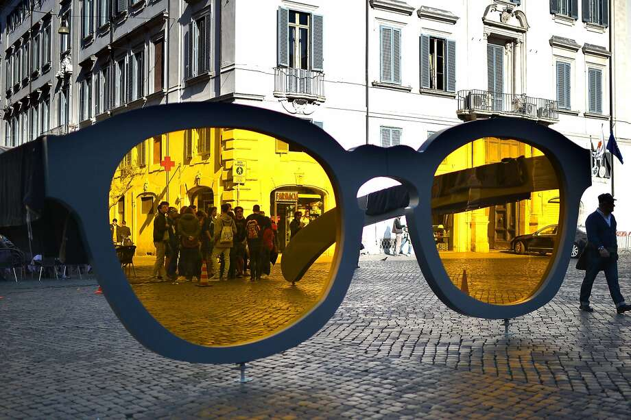 Shady section of the city: Pedestrians pass by giant sunglasses on Piazza Farnese in downtown Rome as part of an 