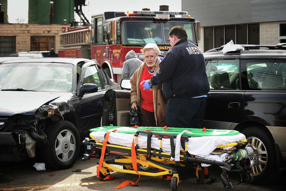 An EMT helps a woman to a waiting stretcher after she crashed her Subaru Outback wagon into a series of seven parked vehicles in the Autozone parking lot at 300 North Avenue in Bridgeport, Conn. on Thursday, March 13, 2014. Photo: Brian A. Pounds / Connecticut Post