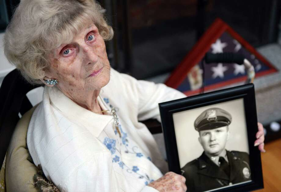 Anna Chmura holds a photo of her late husband, Joseph Chmura, a former Trumbull police officer and retired Board of Education maintenance worker, Friday, Mar. 7, 2014, at her home in Trumbull. Chmura, a former Democratic assistant registrar of voters in Trumbull, has been fighting the town for five years to regain her husband's pension benefits.  The town, which lost the paperwork on the benefits in question, claim instead that they overpaid to the tune of $90,000. Photo: Autumn Driscoll / Connecticut Post