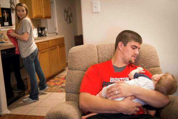 University of Houston football player Rowdy Harper cradles his 8-month-old son Jax as his wife Katie prepares a bottle in the kitchen of their home on Tuesday, March 11, 2014, in Houston. College presidents are working quietly on details of a change in college athletics that will benefit the richest programs and, to a point, reward the student-athletes who help fuel the billion-dollar business of amateur sports. Harper, a senior-to-be offensive lineman at Houston, depends on his wife and her family to help make ends meet. UH estimates the value of a full athletic scholarship for an out-of-state resident living off campus at $30,675.50 and the average cost of attendance for the same student at $35,254.56 - a gap of almost $5,000 per year.
