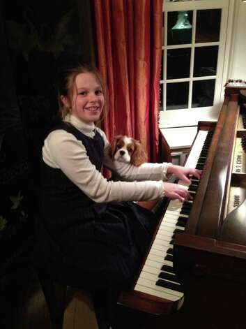 Mary Wrotniak, 10, of Mount Vernon, N.Y., granddaughter of Marilyn and Peter Primomo of Loudonville plays piano with her puppy, Champ, who is happily enjoying the music. (Patricia Wrotniak of Colonie)