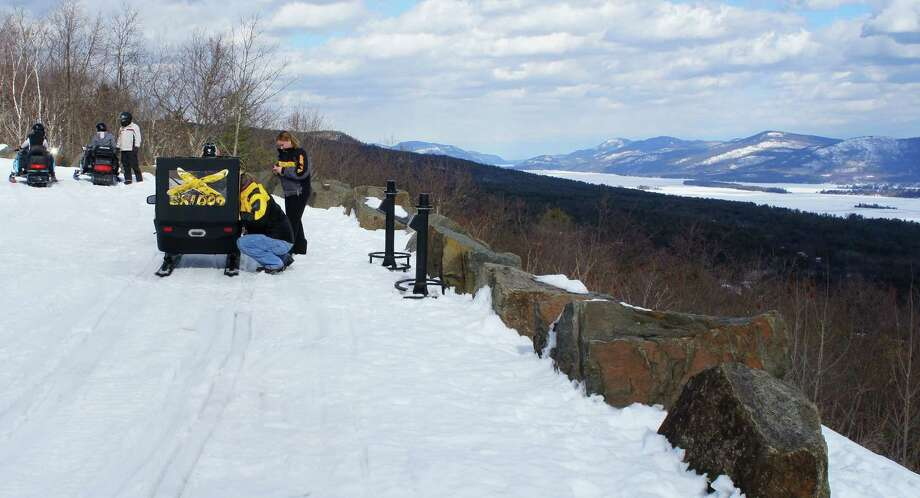 Photo by Herb Terns. Snowmobilers check on their tot, tucked in a Skidoo trailer, at an overlook on the Prospect Mountain road. Photo: Picasa
