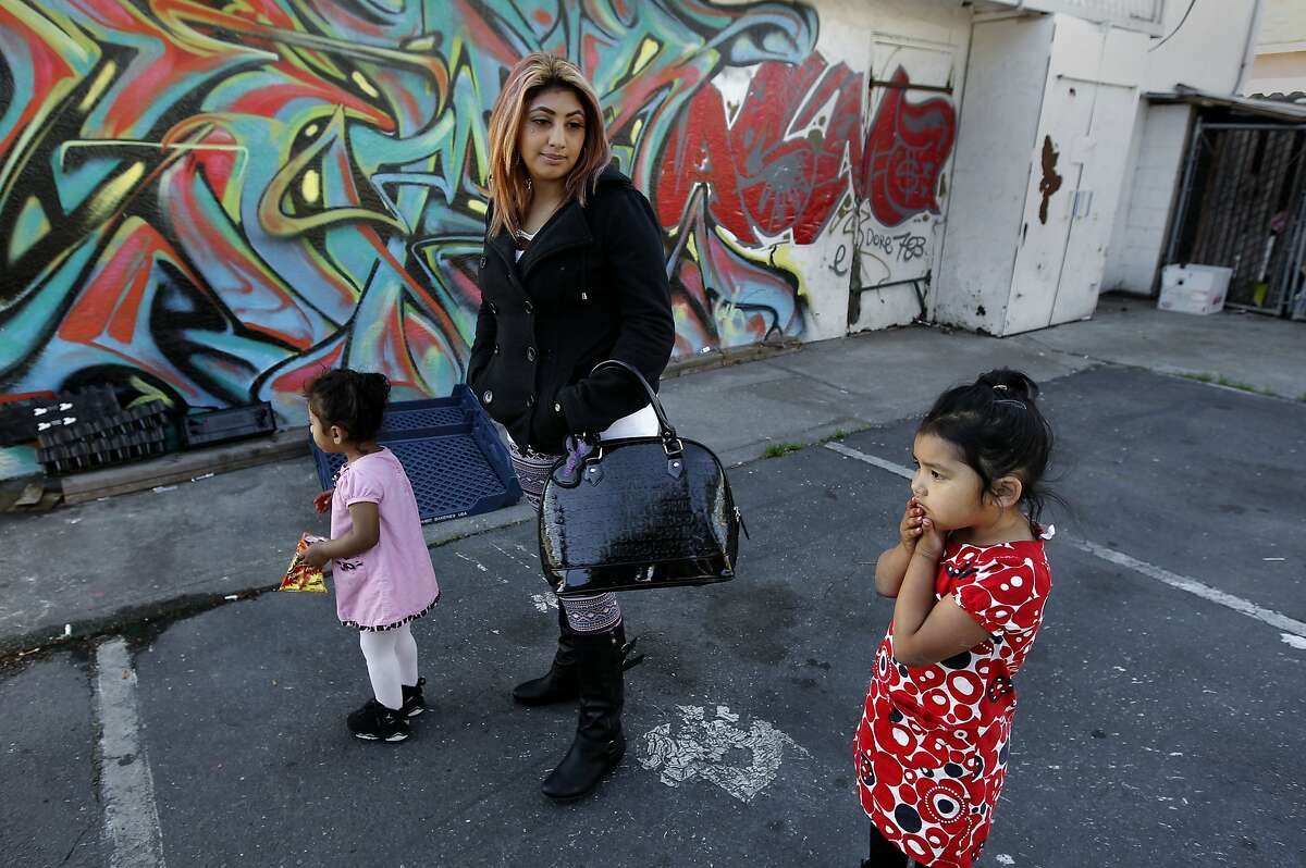 Rosa Escalante waits with her 2-year-old daughter, Isabella (left), and Leilanie, 3, at 82nd and Bancroft avenues in Oakland.