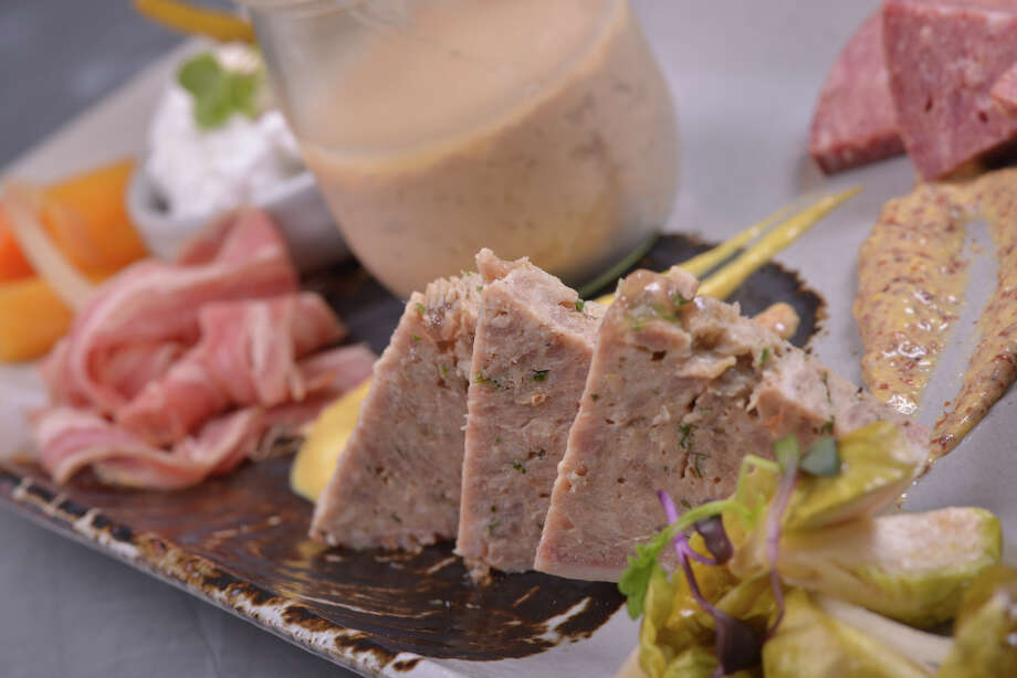 A charcuterie plate from Cured featuring mortadella, chicken liver mousse, jalapeno sauce, apple red wine jam, pickled bussel sprouts, country style pork pate', smoked veal wurst, smoked lamb belly, and whipped pork butter and beer flatbread. Photo: For The San Antonio Express-News