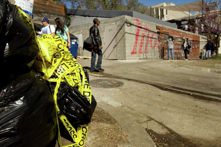 Crime scene tape near the scene Thursday March 13, 2014, of the tragic accident when Rashad Charjuan Owens, 22, of Killeen, drove a vehicle past barricades and into a crowd of people at Red River and Ninth Streets in downtown Austin, Texas. The crash killed two people and injured 23 more. Photo: Laura Skelding, Associated Press / Austin American-Statesman