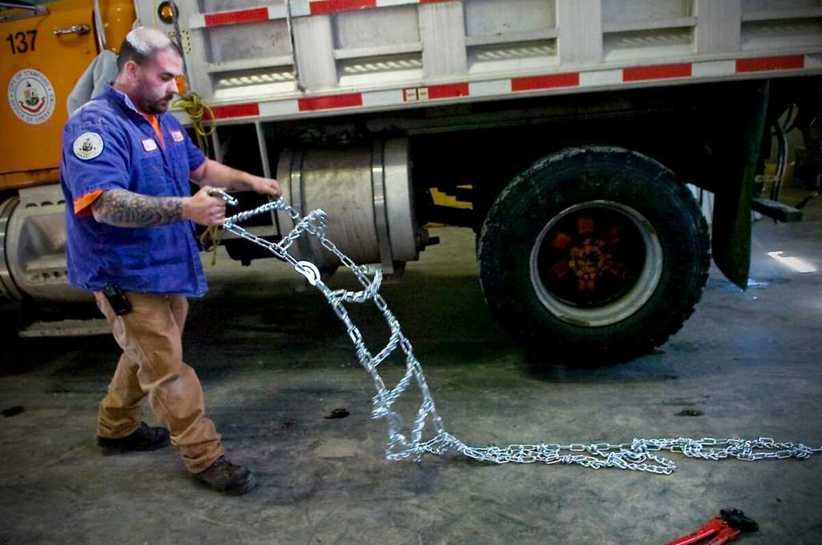 Donnie Lavoie, an employees of the city of Stamford operations department, puts chains on tires in preparation for the upcoming snowstorm in Stamford , Conn. on Tuesday, Feb. 9 2010.