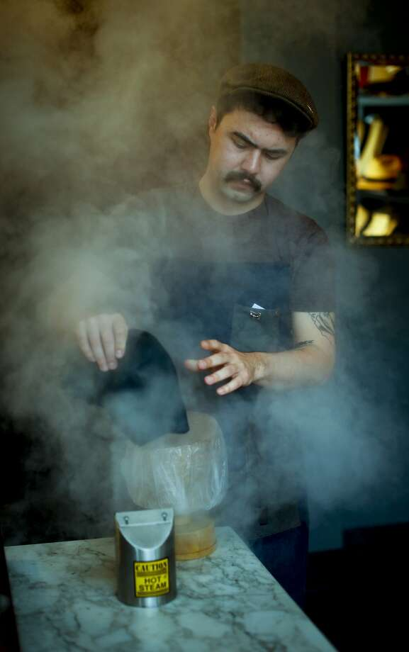 Ron Schiller raises a cloud of steam working on a hat in his shop. Photo: Russell Yip, The Chronicle