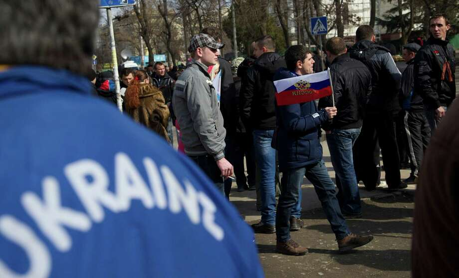 In a March 1 demonstration, a man holds a Russian flag as people gather outside the Parliament building in Simferopol, Ukraine. Russia fever is everywhere in the streets of Crimea as Sunday's vote approaches. Photo: Ivan Sekretarev, STF / AP