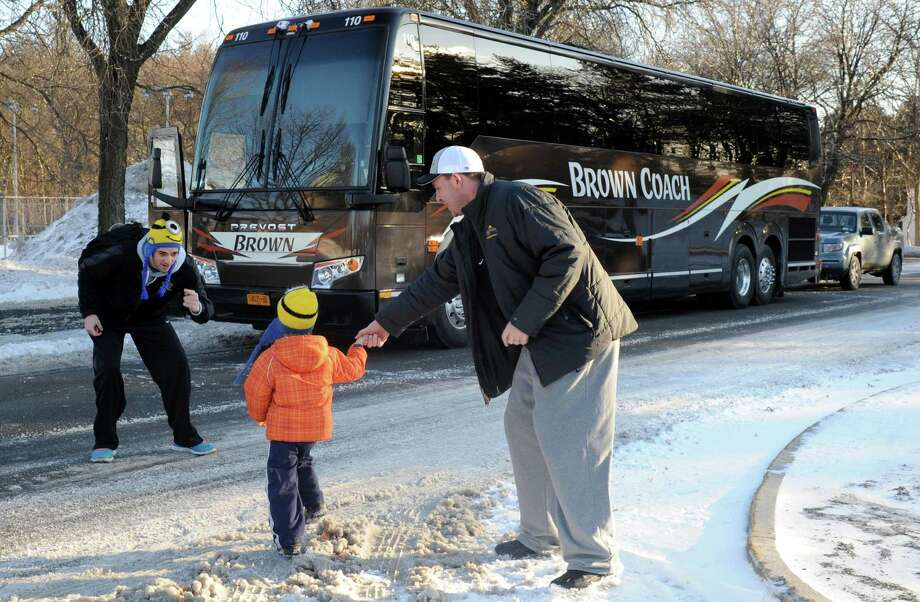 UAlbany head coach Will Brown, right, sends his son Jordan with player Peter Hooley to get on the team bus, out of the cold , as the coach does interviews with local media on Thursday March 13, 2014 in Albany, N.Y. The UAlbany men's basketball team will play Stony Brook in Long Island on Saturday for the America East championship.(Michael P. Farrell/Times Union) Photo: Michael P. Farrell / 00026120A