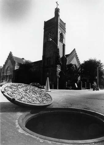 From the May 19, 1982: This brick-lined manhole, with its ornate cover, was built in 1890, predating by three years the completion of the adjacent Christ Church Cathedral, at Texas and Fannin. The standard size for modern manholes, made of precast steel-reinforced concrete, is six feet wide, 12 feet long and seven feet high. Southwestern Bell has more than 10,000 manholes in Houston with tunnels carrying more than 22,000 miles of cable. Photo: Houston Chronicle / Houston Chronicle