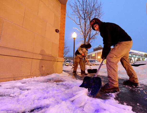 Robi Henry, foreground and Ryan Aubin of the Cleveland Bros. Co. scrape the ice crusted snow from the front of a business on Broadway early Thursday morning, March 13, 2014, in Saratoga Springs, N.Y.      (Skip Dickstein / Times Union) Photo: SKIP DICKSTEIN / 00026147A