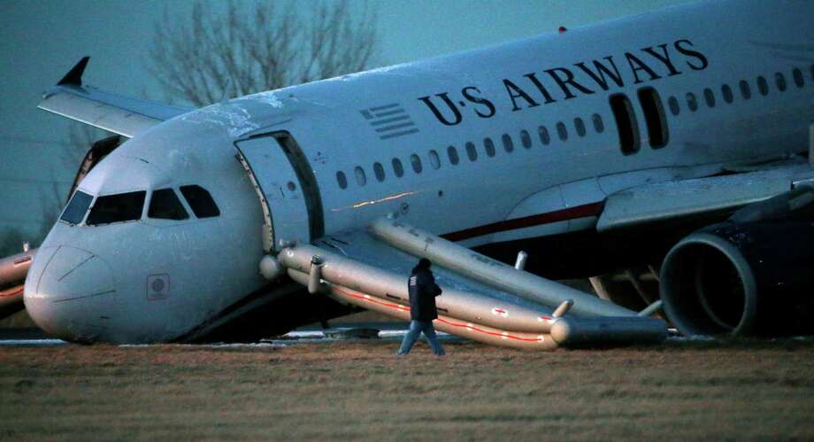 A person walks around a damaged US Airways jet at the end of a runway at the Philadelphia International Airport, Thursday, March 13, 2014, in Philadelphia. Airline officials said the flight was heading to Fort Lauderdale, Fla., when the pilot was forced to abort takeoff around 6:30 p.m., after the front landing gear failed. An airport spokeswoman said no injuries have been reported. (AP Photo/Matt Slocum) Photo: Matt Slocum, STF / AP