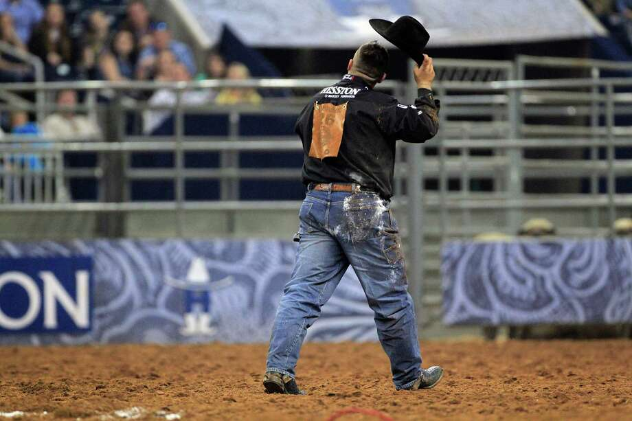 Luke Branquinho tips his hat after taking down a steer in 5.4 seconds earning him a first place in the Steer Wrestling event during the first round of the BP Super Series lV at Rodeo Houston in Reliant Stadium Thursday, March 13, 2014, in Houston. Photo: Johnny Hanson, Houston Chronicle / © 2014  Houston Chronicle