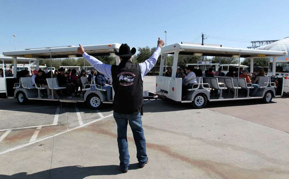 Michael Iglesias gives the thumbs-up to a parking tram filled with rodeo patrons on their way to Reliant Park and RodeoHouston. Photo: Billy Smith II, Staff / © 2014 Houston Chronicle