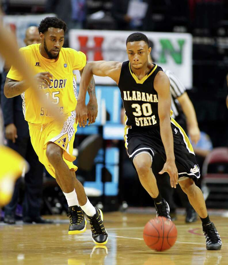"""Toyota Center--action from SWAC basketball tournament. 2nd half action, Alabama State """"Hornets"""" (in black) against Alcorn State """"Braves"""" (in yellow). Alabama State won 64-51. ID: Alabama #30 Terrance LeFlore brings the ball down court pursued by Alcorn #15 LeAntwan Luckett. 2/13/14 Photo: Craig Hartley, For The Chronicle / Copyright: Craig H. Hartley"""