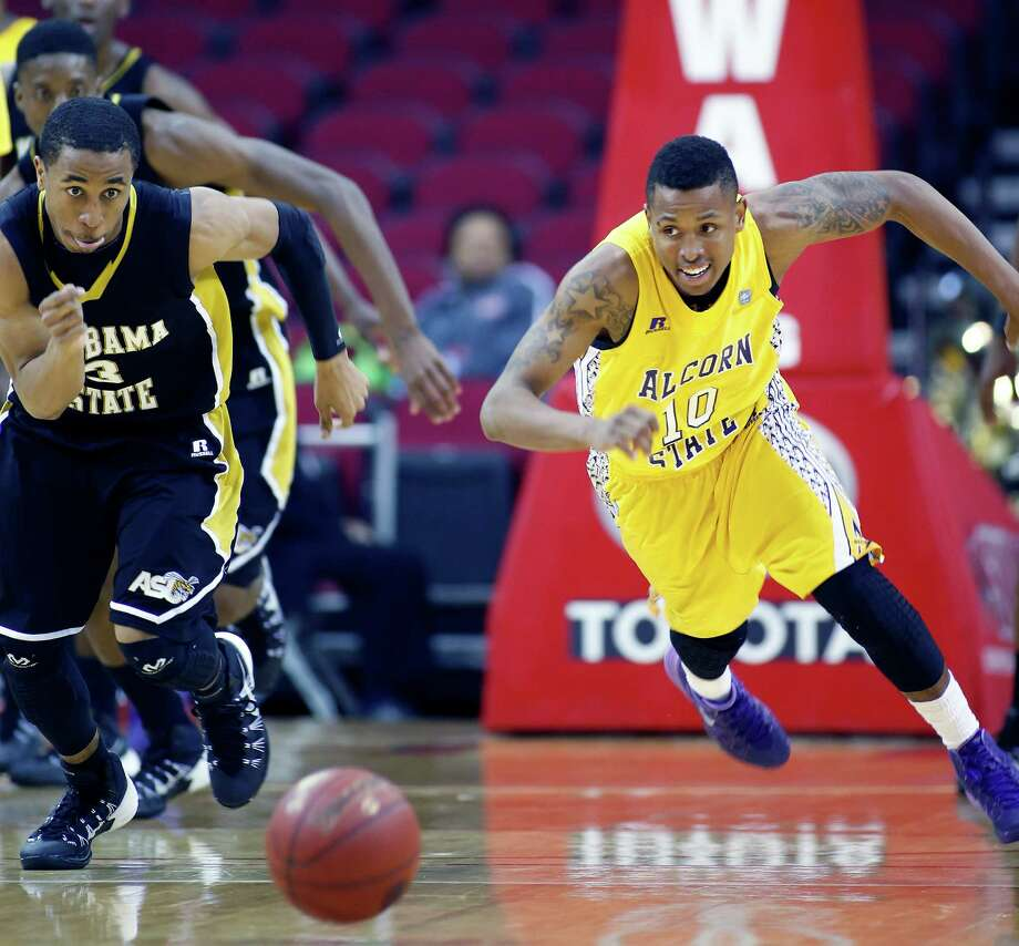 """Toyota Center--action from SWAC basketball tournament. 2nd half action, Alabama State """"Hornets"""" (in black) against Alcorn State """"Braves"""" (in yellow). Alabama State won 64-51. ID: Alabama State #3 DeMarcus Robinson and Alcorn State #10 Devante Hampton scramble for a loose ball. 2/13/14 Photo: Craig Hartley, For The Chronicle / Copyright: Craig H. Hartley"""