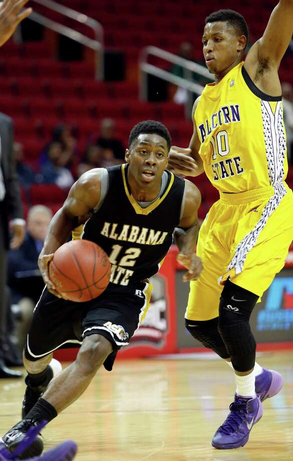 """Toyota Center--action from SWAC basketball tournament. 2nd half action, Alabama State """"Hornets"""" (in black) against Alcorn State """"Braves"""" (in yellow). Alabama State won 64-51. ID: Alabama #12 Jamel Waters scrrambles his way past Alcorn #10 Devante Hampton's defense. 2/13/14 Photo: Craig Hartley, For The Chronicle / Copyright: Craig H. Hartley"""