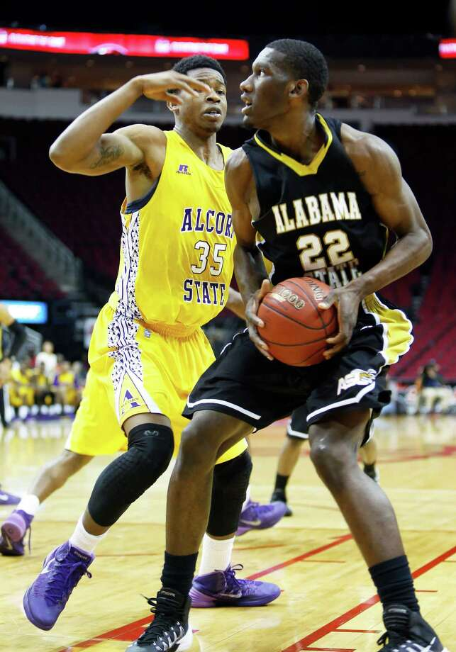 """Alabama State 64, Alcorn State 51Toyota Center--action from SWAC basketball tournament. 2nd half action, Alabama State """"Hornets"""" (in black) against Alcorn State """"Braves"""" (in yellow). Alabama State won 64-51. ID: Alabama #22 Maurice Strong looks for a shot past Alcorn #35 Octavius Brown. 2/13/14 Photo: Craig Hartley, For The Chronicle / Copyright: Craig H. Hartley"""