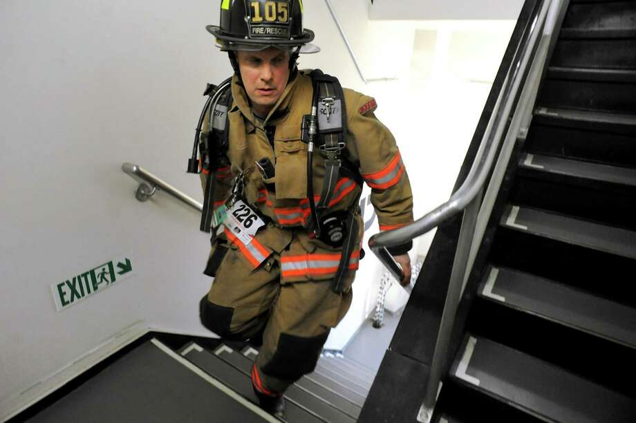 Slingerlands firefighter Nick Behuniak starts climbing 10 flights in the first leg of the Firefighter's Challenge Relay on Thursday, March 13, 2014, at the Corning Tower in Albany, N.Y. The relay is part of the 26th Annual Stair Climb to benefit Cystic Fibrosis Foundation of Northeastern New York. (Cindy Schultz / Times Union) Photo: Cindy Schultz / 00026088A