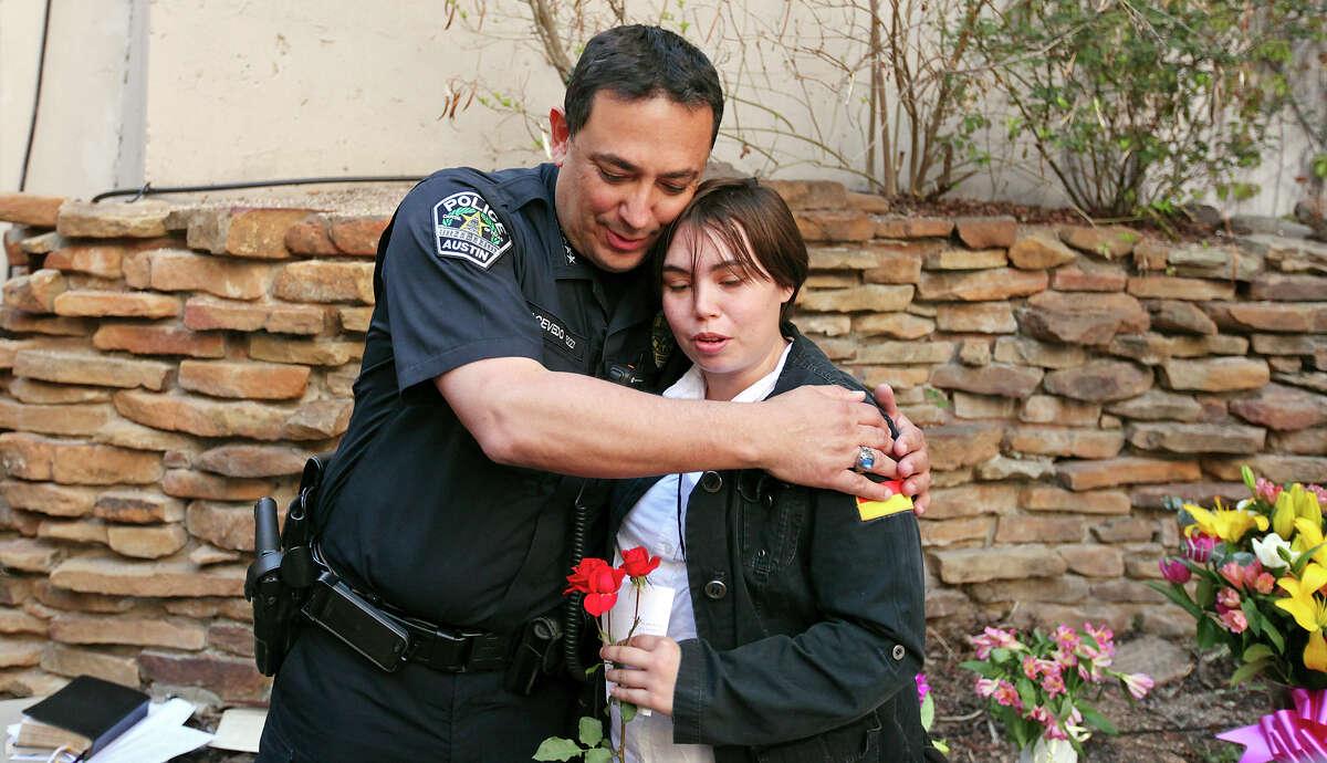 Festivalgoer Kristin Day gets a hug from Police Chief Art Acevedo during a vigil Thursday in Austin.