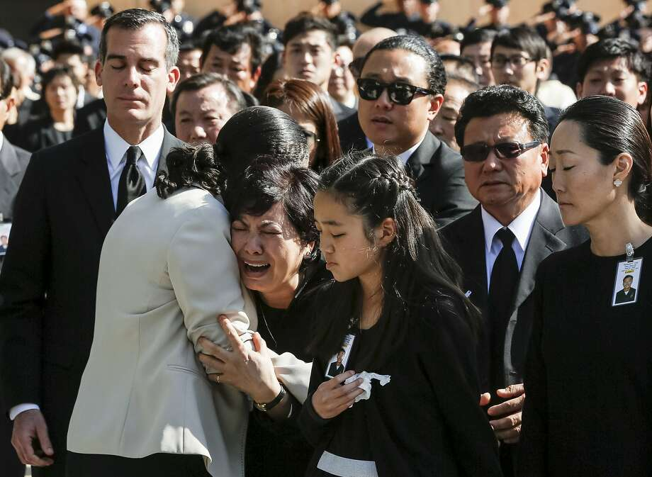 Choung Ja Lee, third from left, mother of fallen Los Angeles Police Department Officer Nicholas Choung Lee, is helped by an LAPD police officer as her son's casket leaves a funeral Mass at the Cathedral of Our Lady of the Angels in Los Angeles, Thursday, March 13, 2014. Others from left include Los Angeles Mayor Eric Garcetti, Lee's daughter Jalen, middle front, brother Danny, center rear, father Heung Jae Lee, and wife Cathy Kim, right. Lee, 40, died when the squad car he and his partner were in collided with a trash truck in Beverly Hills on March 7. (AP Photo/Damian Dovarganes) Photo: Damian Dovarganes, Associated Press