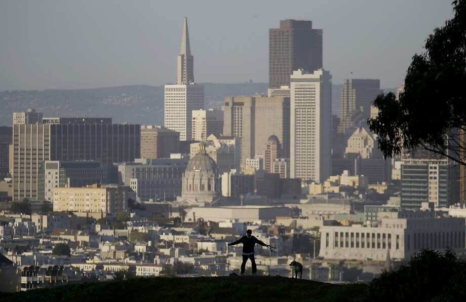 A man walks his dog at Kite Hill Open Space with downtown San Francisco at rear on Thursday, March 13, 2014. (AP Photo/Jeff Chiu) Photo: Jeff Chiu, Associated Press