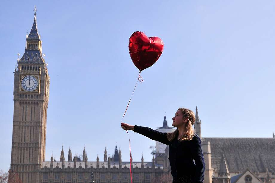 """TOPSHOTS  9 year-old Mili Baxter releases a red balloon in front of the Houses of Parliamnent in central London on March 13, 2014 in a recreation of British artist Banksy's """"Girl with Red Balloon"""" to mark the 3rd anniversary of the Syria crisis. The recreation of Banksy's iconic artwork in front of London's parliament was echoed with simultaenous stagings in the US, Russia, France and Jordan organised by the #WithSyria campaign to mark three years since the start of the conflict in Syria which the Syrian Observatory for Human Rights says has killed more than 140,000 people. AFP PHOTO / CARL COURTCARL COURT/AFP/Getty Images Photo: Carl Court, AFP/Getty Images"""