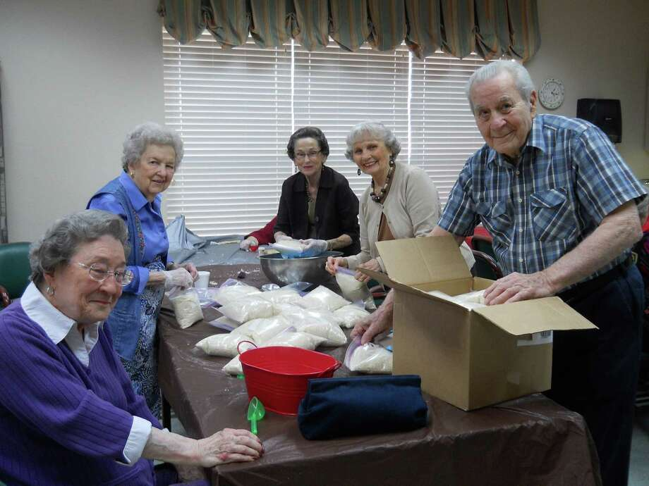 Parkway Place residents, (left to right) Mary Nell Benson, Frances Fagg, Rena Epps, Mauvirine Sorrell and Merrel Schilling, bag rice for the Houston Food Bank to help families in need.