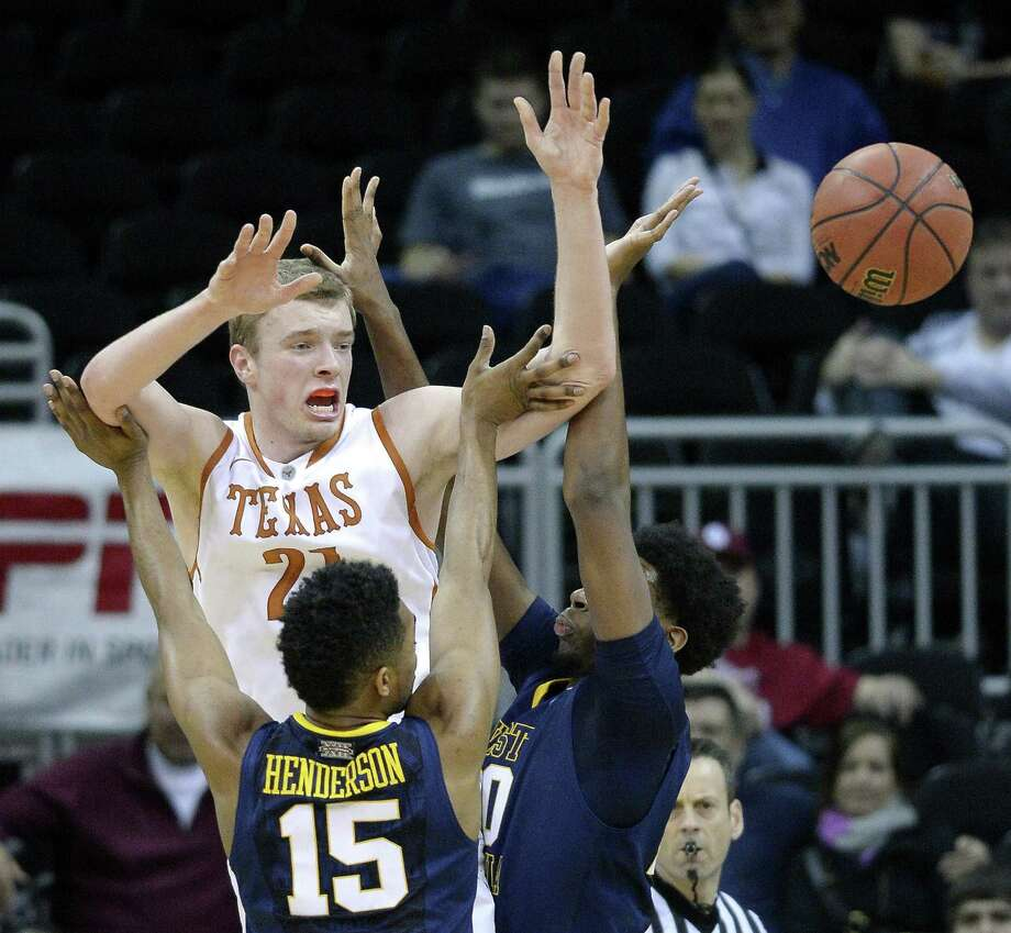 Texas' Connor Lammert (21) passes over the defense of West Virginia's Terry Henderson (15) and Brandon Watkins during the quarterfinals of the Big 12 Tournament at the Sprint Center in Kansas City, Mo., on Thursday, March 13, 2014. Texas advanced, 66-49. (John Sleezer/Kansas City Star/MCT) Photo: JOHN SLEEZER, McClatchy-Tribune News Service / Kansas City Star