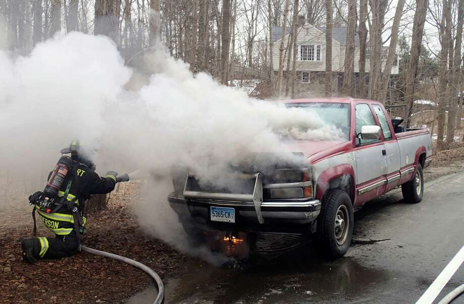 Firefighters extinguish a fire that erupted in the engine compartment of a pickup truck Friday morning on Weston Road. Photo: Contributed Photo / Westport News