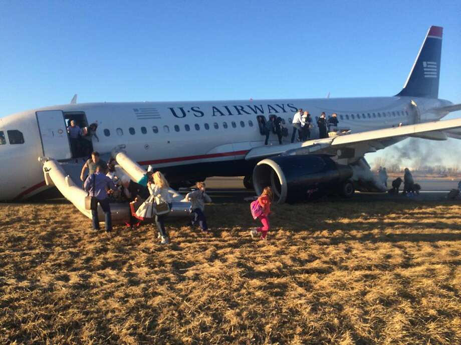 Passengers flee from US Airways Flight 1702 after the pilot was forced to abort takeoff when a tire on the plane's front landing gear blew out in Philadelphia. Photo: Dennis Fee, Associated Press