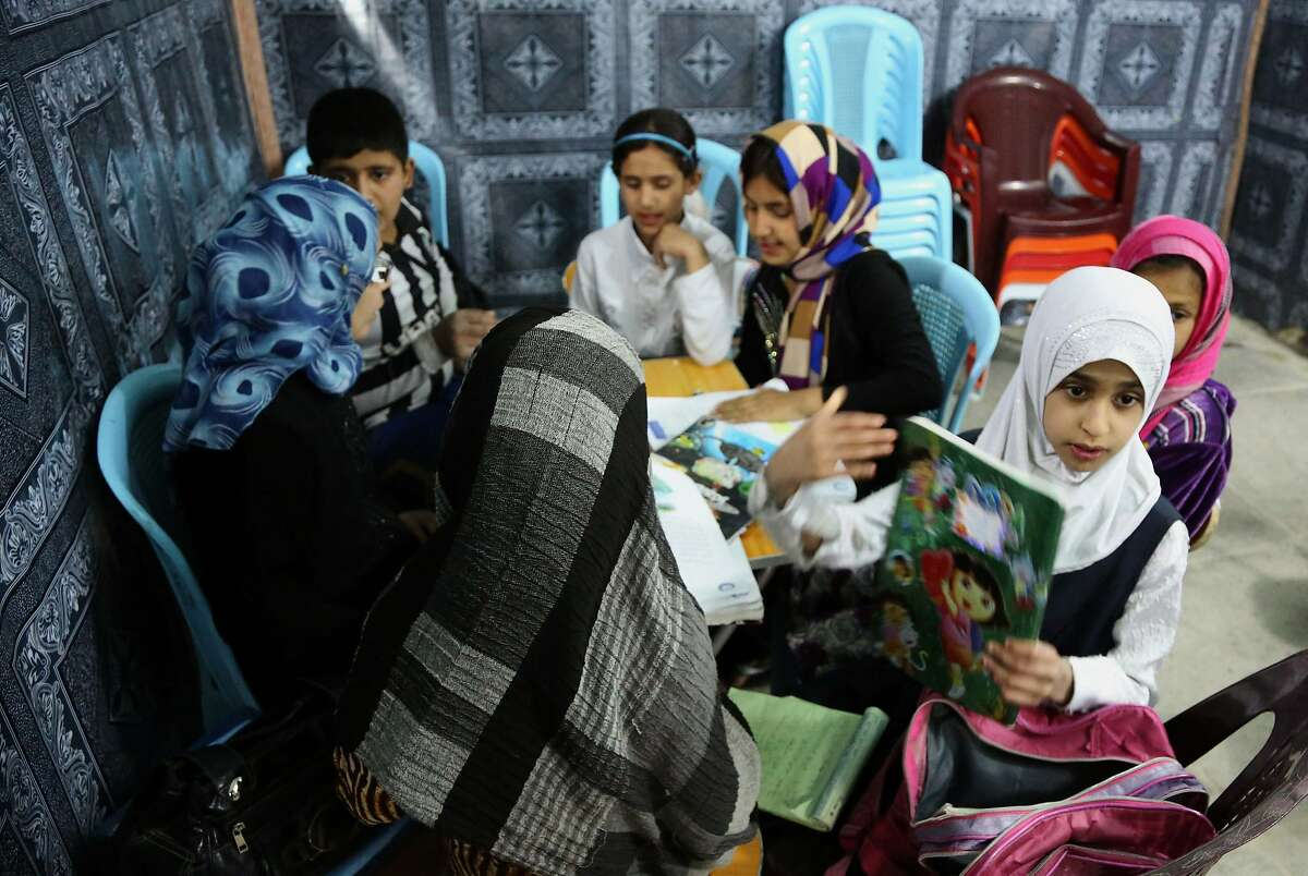 Iraqi girls study at an orphanage in Baghdad. The director of the shelter says she will not allow child marriages.