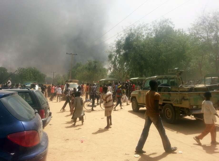 Residents walk along a street as smoke rises after Boko Haram Islamist militants attacked a military base in the northeastern city of Maiduguri. Photo: Str, AFP/Getty Images