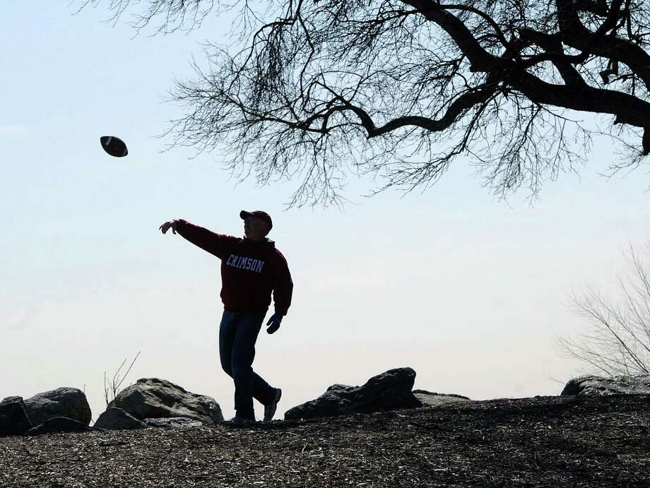 Gary Anstey of Cos Cob enjoys the sunny 45 degree weather by tossing a football to his son, Stephen Anstey(not pictured), while having a catch at Greenwich Point, Friday, March 14, 2014. Photo: Bob Luckey / Greenwich Time