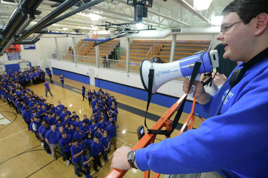 Class President Jose Alves directs the students and faculty attempting to break the Guinness record for world's largest human Pi symbol in the gym at Henry Abbott Technical School in Danbury, Conn. Friday, March 14, 2014.  448 students and faculty members participated, staying in formation of the math symbol for 15 minutes as several cameras recorded the world record attempt.  The current record is 250 and the school will send the footage to Guinness to be reviewed to the new world record. Photo: Tyler Sizemore / The News-Times