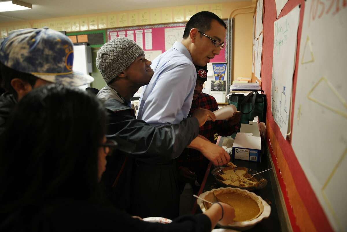 June Jordan School for Equity geometry teacher, Marcus Hung (second from right), gets caught in the middle as Omari Major (third from right), 15 and Jahmal Bolãnos (right), 15, get playful when they both end up with their hands on a plate of pie while celebrating Pi Day at June Jordan School for Equity on Friday, March 14, 2014, in San Francisco, Calif.