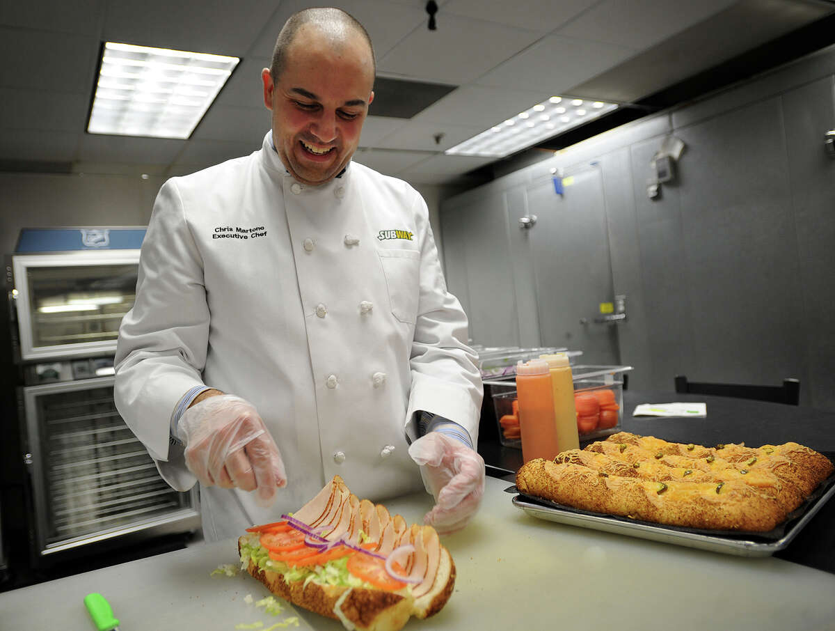 Corporate Executive Chef Chris Martone builds a footlong turkey sub on the company's new jalapeno cheese bread in the test kitchen at Subway headquarters in Milford.