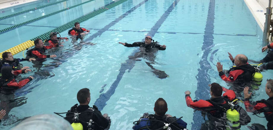 Instructor Ed Hayes, center, teaches diving techniques to emergency responders from Greenwich, Stamford and other communities in the Greenwich Boys and Girls Club pool. Photo: Contributed Photo, Tom Etense/Contributed Photo / Greenwich Time Contributed