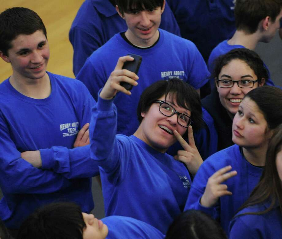 Stephanie Vivas takes a selfie while participating with other students and faculty in an attempt to break the Guinness record for world's largest human Pi symbol at Henry Abbott Technical School in Danbury, Conn. Friday, March 14, 2014.  448 students and faculty members participated, staying in formation of the math symbol for 15 minutes as several cameras recorded the world record attempt.  The current record is 250 and the school will send the footage to Guinness to be reviewed to the new world record. Photo: Tyler Sizemore / The News-Times