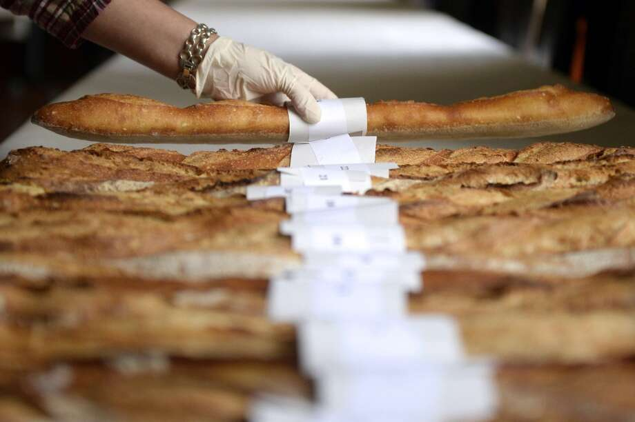 France: A view of French 'baguette' breads with number tags ahead of their consideration by a jury in the 'Best baguette of Paris' contest, on March 13, 2014, in Paris. Hundreds of bakers in the French capital compete in the annual contest, hoping to win the coveted 'Best baguette of Paris' title. Photo: MARTIN BUREAU, AFP/Getty Images